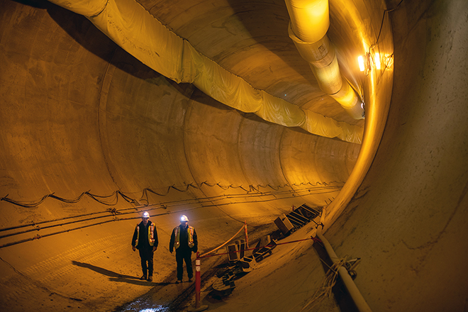 Workers walk through a segment of one of the diversion tunnels, recently lined with concrete.