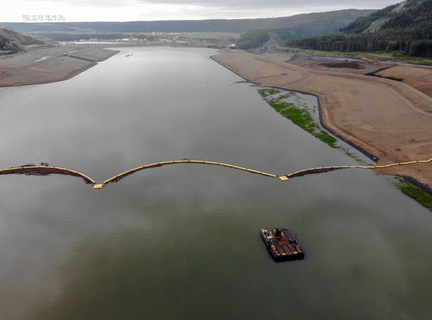 An aerial view of the headpond and debris boom where a spud barge is used for clearing debris materials from the boom. (July 2021)