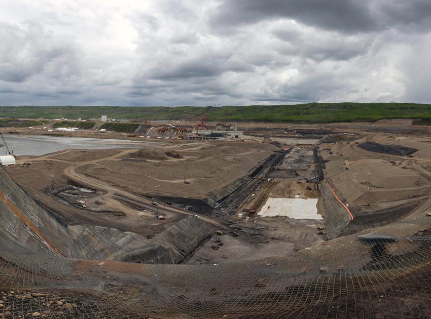 South-facing view of the dam core trench. The white tarps are covering stockpiled dam core till materials. (May 2021)