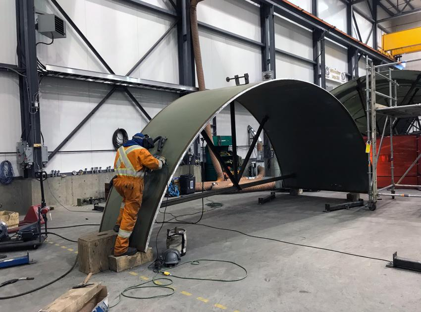 A welder works on part of the spiral case in our on-site turbines and generators manufacturing facility. (January 2019)