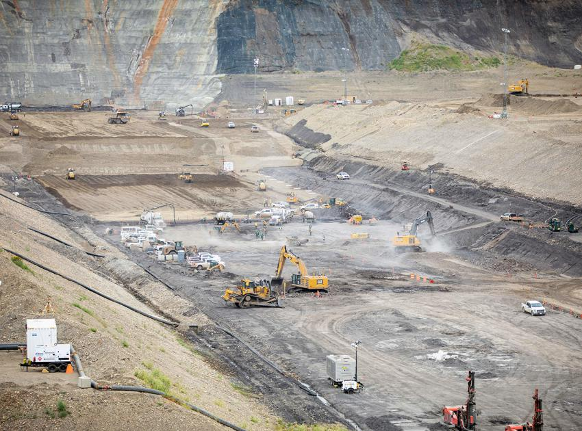Crews prepare the left bank and remove of a top shale bedrock layer, to prepare for glacial till placement. (July 2021)