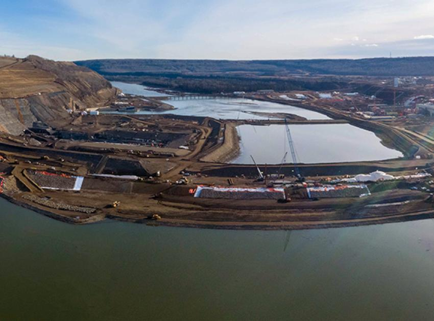 The completed upstream cofferdam diverts the Peace River around the main dam construction area through two tunnels in the river's north bank. (October 2020)