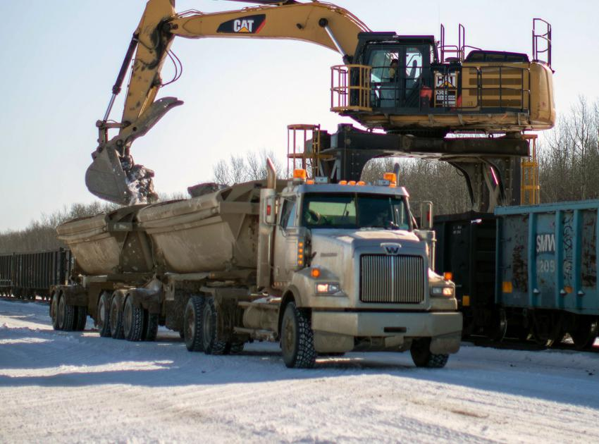 A side-dump truck is loaded with rip-rap, which is hauled to site to stockpile for river diversion. (April 2020)
