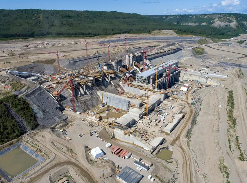 Spillway and powerhouse construction are ongoing with the Roller-Compacted Concrete (RCC) Buttress and the approach channel in the background. (July 2021)