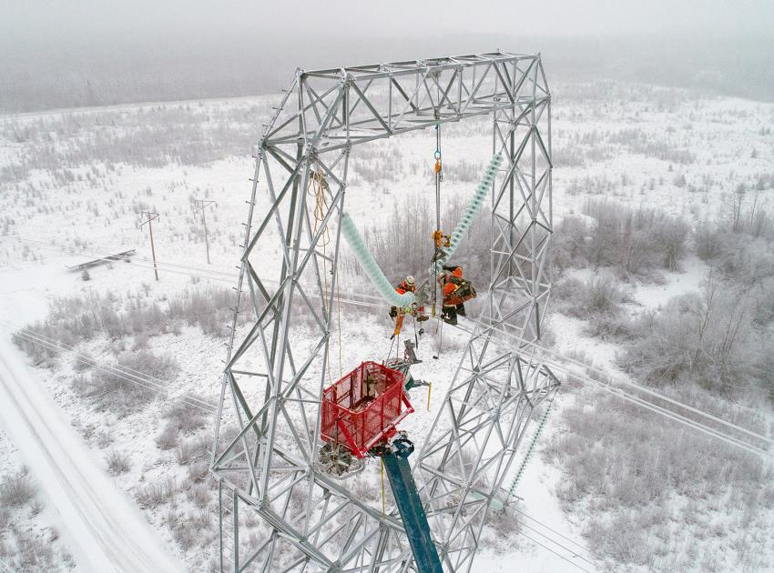 Power line technicians clip conductors into the new transmission line insulator assembly. (December 2019)