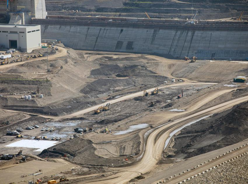 Aggregate material is filtered and placed in the dam's downstream shell. At centre, the top layer is removed to access the bedrock layer in the core trench. (July 2021)