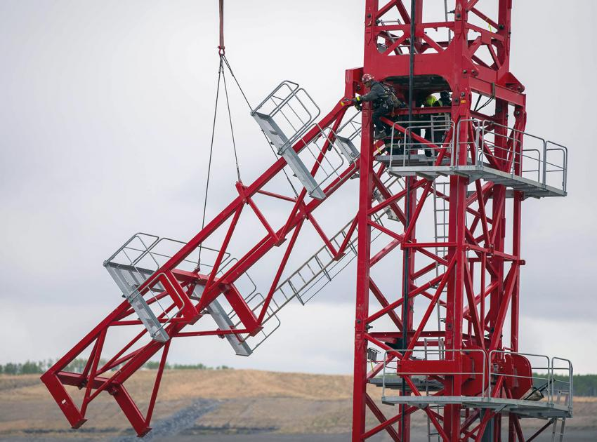 Dismantling the access assembly platforms on a newly erected tower crane at the spillway basin. (May 2021)