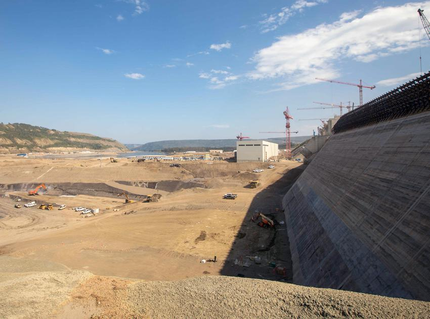 Moving material near the dam and core roller-compacted concrete buttress. (August 2021)