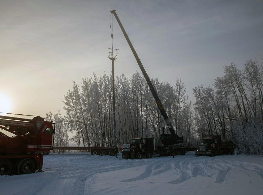 The 18-metre-long pole is hoisted into position and the base is encased in a concrete foundation. (November 2020)