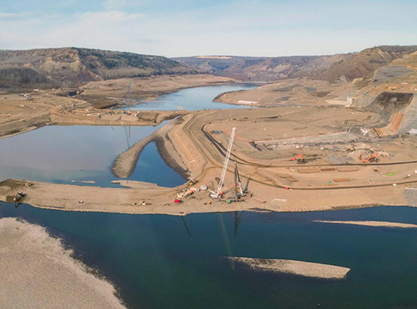 The downstream cofferdam is under construction as the Peace River exits the diversion tunnels. (October 2020)