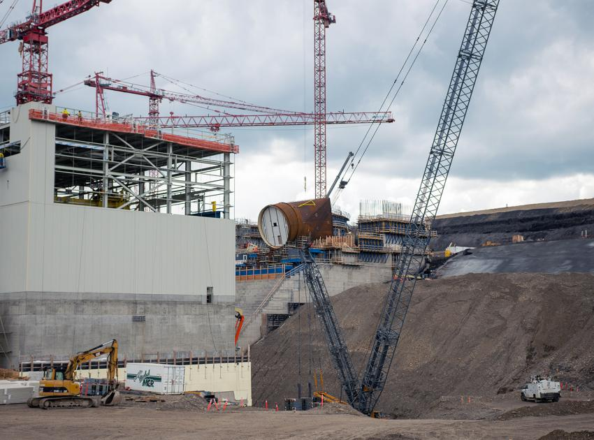 View from the west side of the main service bay where the Unit 1 penstock intake piece is being lifted for installation. (Summer 2019)