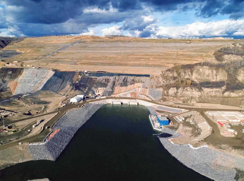 The Peace River flows out of the diversion tunnels near the temporary upstream fish passage facility (blue building). (October 2020)