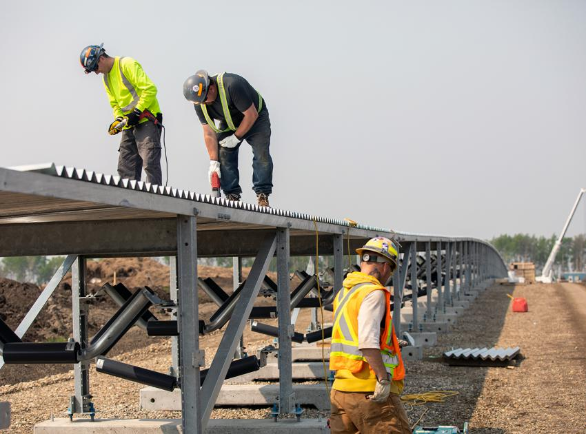 Workers install overhead cladding to protect the till conveyor belt. (Spring 2019)