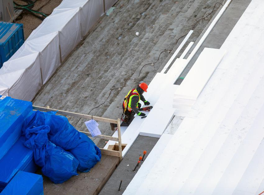 A worker insulates the steps and slope of the powerhouse buttress. As it gets colder outside it is necessary to reduce the temperature difference between the core and the surface of the concrete to prevent cracking. (October 2019)