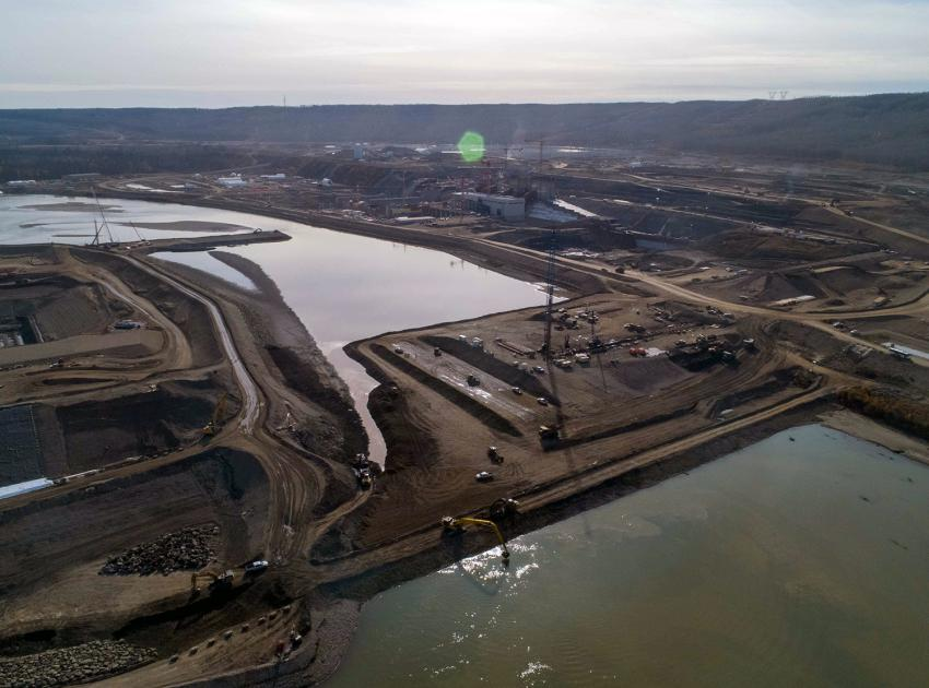 The completion of the rockfill berm officially marked the beginning of the project's river diversion phase; behind the berm, the upstream cofferdam nears full encroachment across the Peace River. (October 2020)