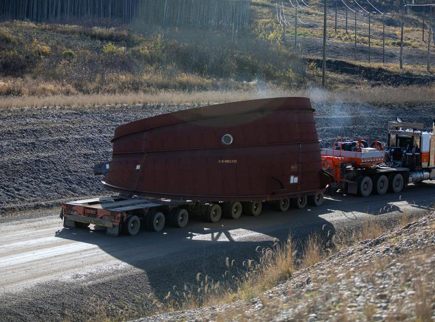 Unit 1 draft-tube elbow, the first of six, is being moved to the main service bay at the powerhouse.  A penstock is a large steel pipe in a hydroelectric generating station that brings water from the reservoir to a turbine.  (October 2020)