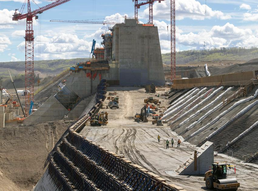 Crews place roller-compacted concrete on the dam and core buttress. (May 2021)