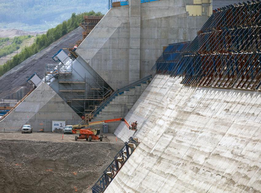 Workers inspect the roller-compacted concrete at the dam and core buttress after the formwork is removed. (June 2021)
