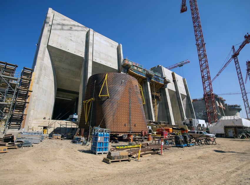 Intake units 1 and 3 are substantially complete, with unit 2 under construction. The unit 4 penstock transition piece is pictured in the foreground. (August 2021)