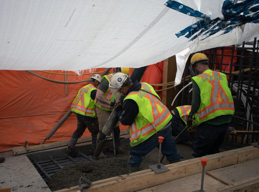 Workers place concrete at the spillway headworks. (April 2021)