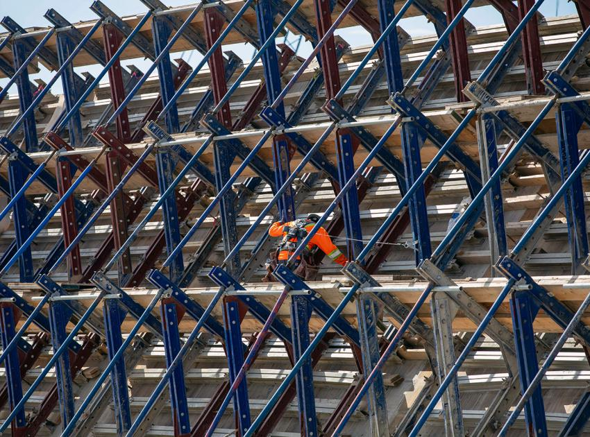 A worker installs roller-compacted concrete formwork between reinforced steel on the south face of the dam buttress. (June 2021)
