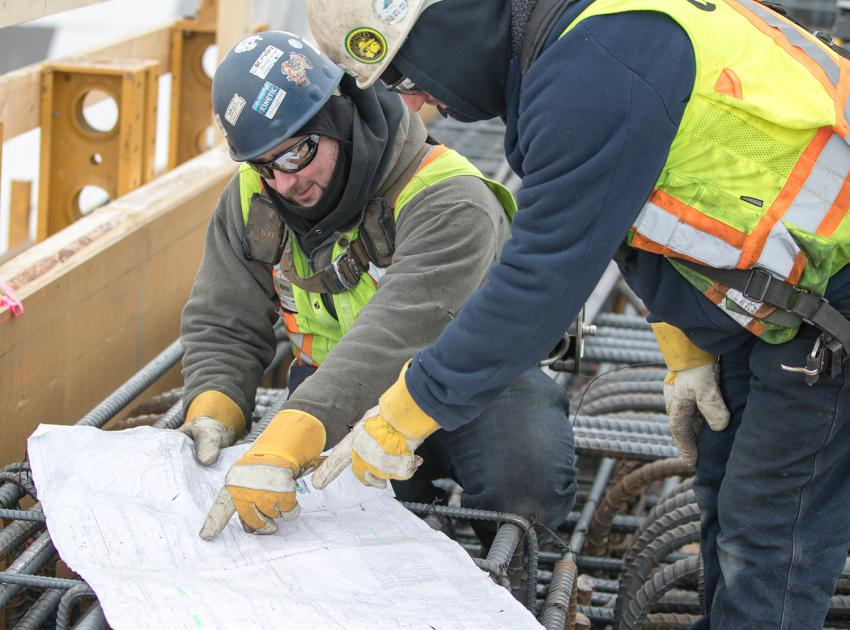 Workers review drawings for the main service bay area. (February 2019)