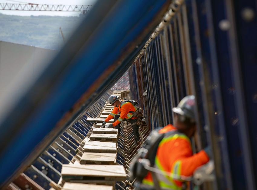 Workers install roller-compacted concrete formwork between reinforced steel on the dam buttress. The distance between the blue cantilever supports is approximately 90 centimetres. (June 2021)