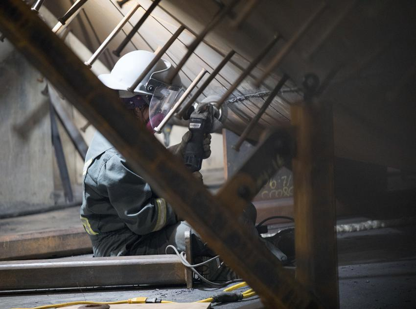 A welder works on a penstock transition segment. Penstocks are 8-metre-wide pipes that move water from the river intakes to the turbines. (January 2019)
