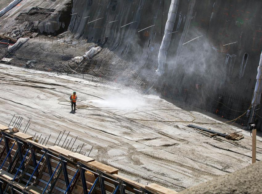 A worker sprays mist on the roller-compacted concrete surface before the next layer of concrete is placed. (May 2021)