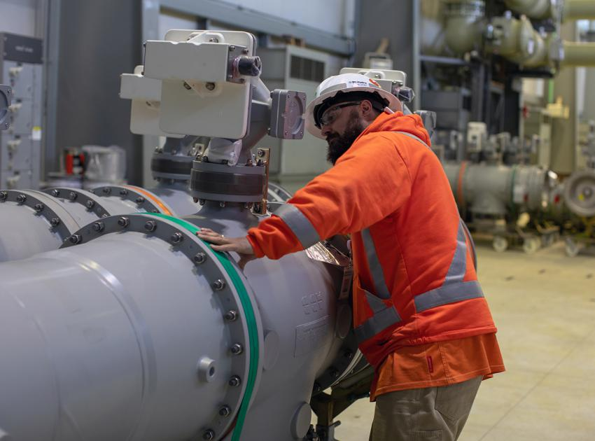 A worker is verifying the nameplate information of the new Gas-insulated Switchgear (GIS) equipment at Peace Canyon. This equipment will be used to connect the new 500 kV Site C transmission lines to the BC Hydro power system. (Spring 2019)
