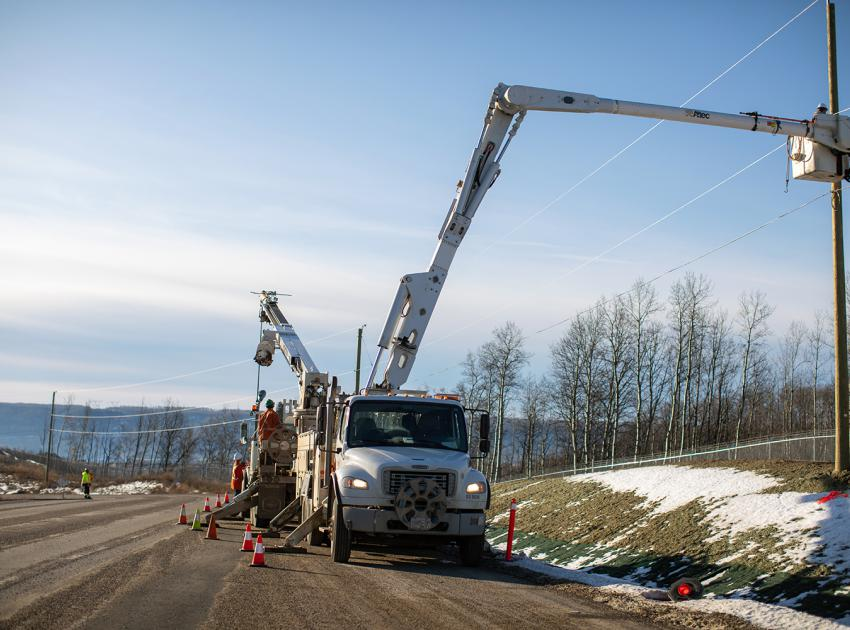 A line crew installs the davit arm and lighting at the Old Fort Rd. chain-up area, which will provide a safe place for trucks to put on and remove chains in the winter months. (November 2019)