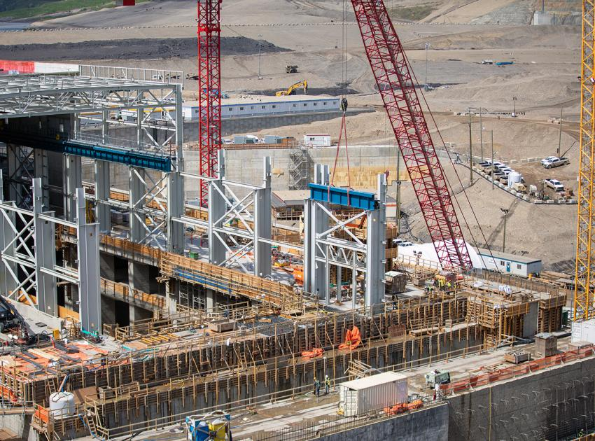 A bridge crane girder section is lowered into position at the auxiliary service bay of the powerhouse. (May 2021)
