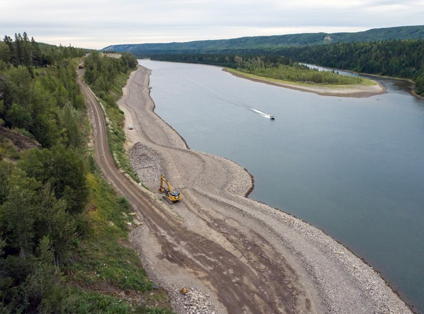 An excavator at the bottom of the DA Thomas Road hill piles riprap on the Hudson's Hope shoreline protection berm. (August 2021)