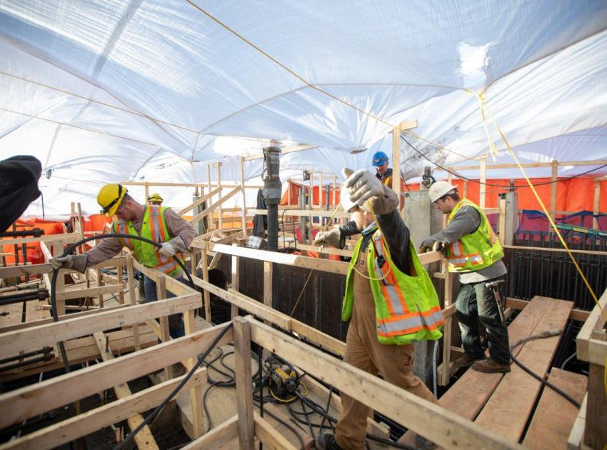 Workers place a concrete slab at the intakes. (March 2020)